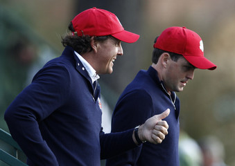 U.S. golfer Mickelson acknowledges the crowds cheers as he arrives on the first tee with Bradley during the morning foursomes round at the 39th Ryder Cup golf matches at the Medinah Country Club