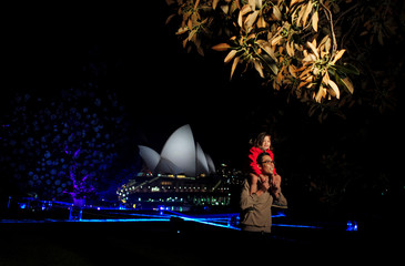 Visitors to the Sydney Botanical Garden's inaugural contribution to the Vivid Sydney light festival walk in front of the Sydney Opera House during a preview of the annual interactive light installation and projection event around Sydney