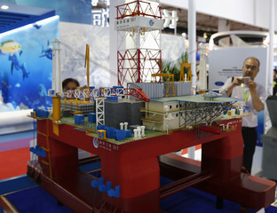 A visitor takes a picture of a scale model of the Chinese oil rig Haiyang Shi You 981 during the China Beijing International High-Tech Expo in Beijing