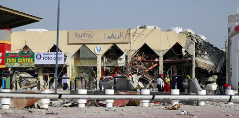 People stand amidst debris near a Turkish restaurant following a gas explosion in Doha