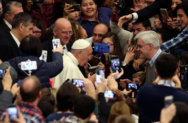 Pope Francis drinks the traditional Argentinian mate drink offered to him by a faithful as he arrives during his Wednesday general audience in Paul VI Hall at the Vatican