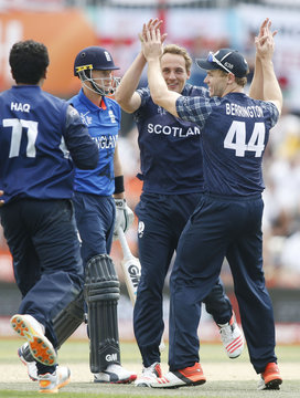England batsman Root leaves the field after being dismissed by Scotland's Davey as he and teammate Berrington celebrate during their Cricket World Cup match in Christchurch