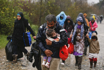 A migrant carries his child after crossing the border from Greece into Macedonia, near Gevgelija
