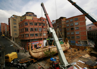 Cranes place 'Viracocha III', a boat made only from totora reeds, on a trailer truck during preparations for the boat to cross the Pacific Ocean, from Chile to Australia on an expected six-month journey, in La Paz, Bolivia