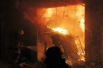 A Civil defence member tries to put out a fire after what activists said was shelling from forces loyal to Syria's President Bashar al-Assad in Aleppo's Al-Mashad neighbourhood