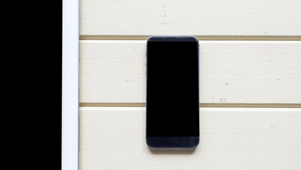 Wall Mural - taplet with smart phone close up on wood background