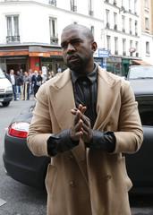 Rapper Kanye West gestures as he arrives with TV personality Kim Kardashian at a fashion designer workshop in Paris