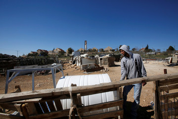 Palestinian man moves a water tank in the village of Umm al-Khair as the Jewish settlement of Karmel is seen in the background, near the West Bank city of Hebron