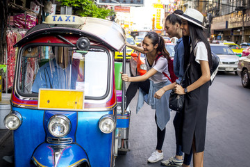 Three asian girls are taking Tuktuk to travel around Chinatown, Thailand