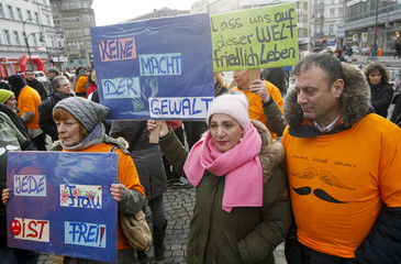 People hold placards during a solidarity demonstration against the violence against women in Berlin