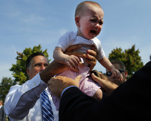 Republican presidential candidate and former Massachusetts Governor Romney passes crying baby back into crowd outside American Legion Post 176