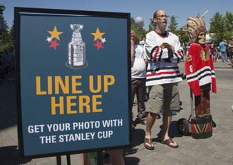 Jerry Ruck stands in line with his Cigar Store statue to have his picture taken with the NHL's Stanley Cup in Surrey