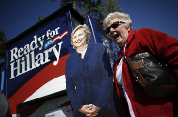 A supporter of former U.S. Secretary of State Hillary Clinton has her picture taken with a cardboard cutout of Clinton at 37th Harkin Steak Fry in Indianola, Iowa