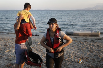 A migrant woman prepares to remove her lifejacket as her husband holds their son, moments after arriving on a dinghy on the Greek island of Kos