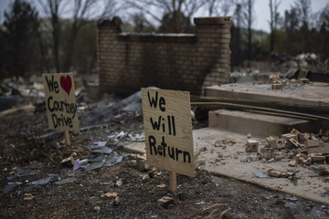 Signs are left by residents outside a house left burned by the Waldo Canyon fire in the Mountain Shadows community of Colorado Springs, Colorado