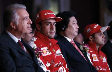 Ferrari Formula One driver Alonso looks on next to Ferrari Vice Chairman Ferrari , Weichai Power company chairman Tan and Ferrari Formula One driver Massa of Brazil during a event
