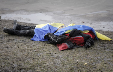 The body of a victim covered by Ukrainian national flags is seen at the site of attack in Kharkiv