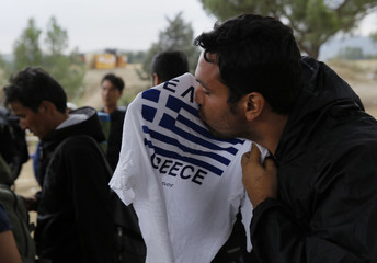 A Syrian refugees kisses a T-shirt featuring the Greek flag moments before crossing Greece's border with Macedonia