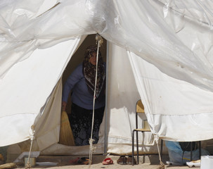 A Syrian refugee cleans up a tent at Reyhanli refugee camp in Hatay