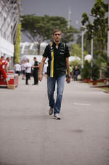 Caterham Formula One driver Petrov of Russia walks in the paddock ahead of the first practice session of the Singapore F1 Grand Prix at the Marina Bay Street Circuit