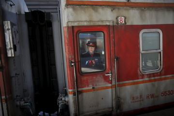 A railway worker looks from inside a train arriving at the Beijing Railway Station during the Chinese Lunar New Year travel rush, as the annual Spring Festival holidays end