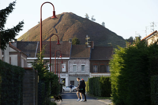 """A couple and their dog walk past traditional northern France brick houses in the neighbourhood of closed metallurgical plant """"Usinor"""" with a slag heap in the background, in Denain"""
