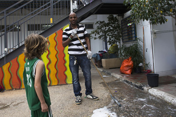 Angesom Solomon, a 28-year-old African migrant from Eritrea, speaks with a boy while cleaning at a school in Tel Aviv