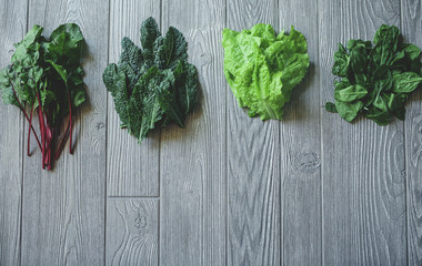 Mixed Greens including Kale, Spinach, Lettuce, and Beet Greens over a wooden table.