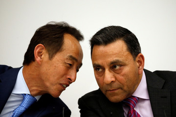 Young Sohn, president and Chief Strategy Officer of Samsung Electronics, talks with Dinesh Paliwal, CEO of Harman International Industries, during a news conference at Samsung Electronics' office in Seoul