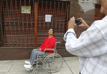 A woman pose for a picture at the exterior of the house on 531 Membrillar Street of the Flores neighbourhood, where then Argentine Cardinal Jorge Bergoglio, now Pope Francis, lived as a child in Buenos Aires
