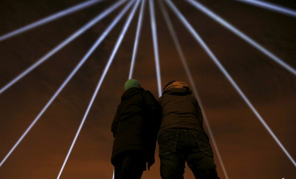 People look up at as blue beams of light are projected during a vigil to remember the victims of a mass shooting in Montreal