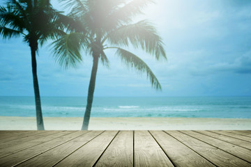 Blur beach background with palm tree and empty wooden.