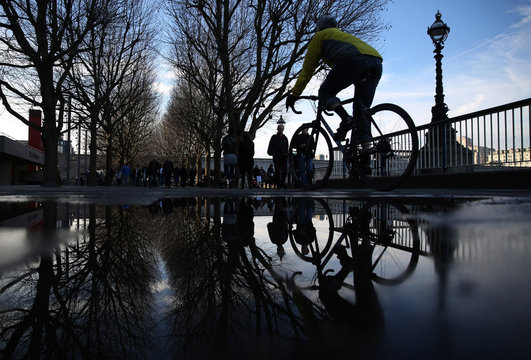 A man is reflected as he cycles along the Southbank on a sunny day in London, Britain