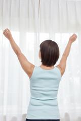 伸びをする中年女性