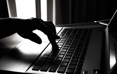 Fototapeta silhouette black and white of anonymous hacker typing on keyboard of laptop for remotely hacking and receiving