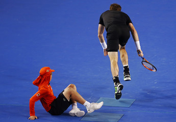 A ballboy falls over as Murray of Britain runs past to chase a shot from Djokovic of Serbia during their men's singles final match at the Australian Open 2015 tennis tournament in Melbourne