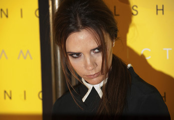 Victoria Beckham poses for photographers as she marks the launch of Victoria, Victoria Beckham line of clothing at the Harvey Nichols store in London