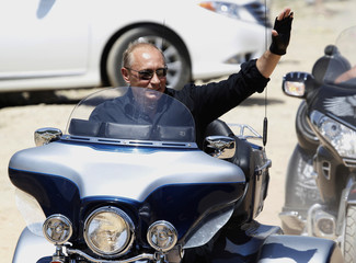 Russia's Prime Minister Vladimir Putin waves while riding a Harley Davidson Lehman Trike near Sevastopol