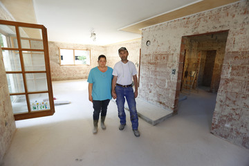 Manuela and Herbert Schmid pose for a picture in their flood-affected living room in Deggendorf after the water soaked and plastering was removed from the walls
