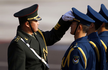 An officer adjusts the hat of a member of an honour guard as he inspects them at Beijing airport