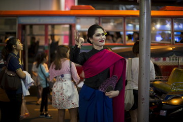 An street artist dressed in a traditional Thai clothing performs in Bangkok