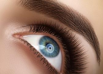 Close-up macro beautiful female eye with extreme long eyelashes. Lash design, natural health lashes. Clean vision