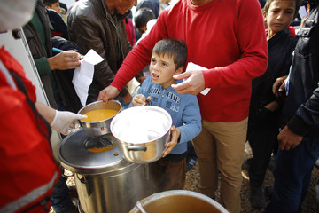 Kurdish refugees from the Syrian town of Kobani queue to get food in a camp in the southeastern town of Suruc