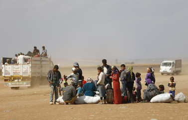 Syrian Kurdish refugees wait after crossing the Turkish-Syrian border near the southeastern town of Suruc in Sanliurfa province