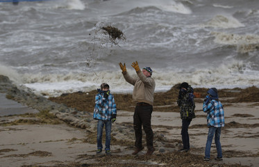 People stand on the North Sea beach near the town of Emden