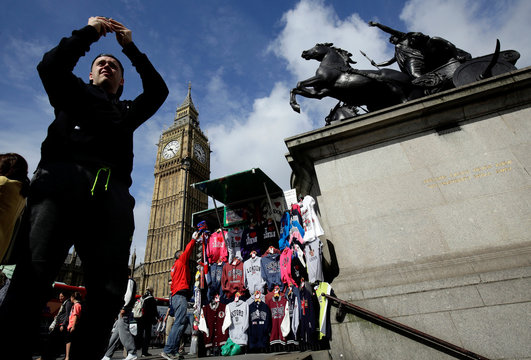 A man takes a picture near the Big Ben clock tower in London