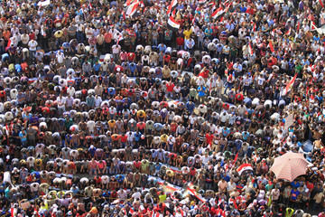 Protesters opposing Egyptian President Mohamed Mursi attend evening prayers during a protest at Tahrir Square in Cairo