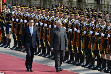 Indian Prime Minister Narendra Modi and Chinese Premier Li Keqiang review an honour guard during a welcome ceremony outside the Great Hall of the People in Beijing