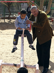 Doctor Muhammad Judeh helps Othman play in a public park as part of his treatment in Amman