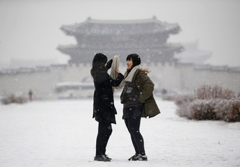 A woman helps her friend to adjust her scarf during snowfall in winter, as Gyeongbok Palace is pictured in the background, in central Seoul